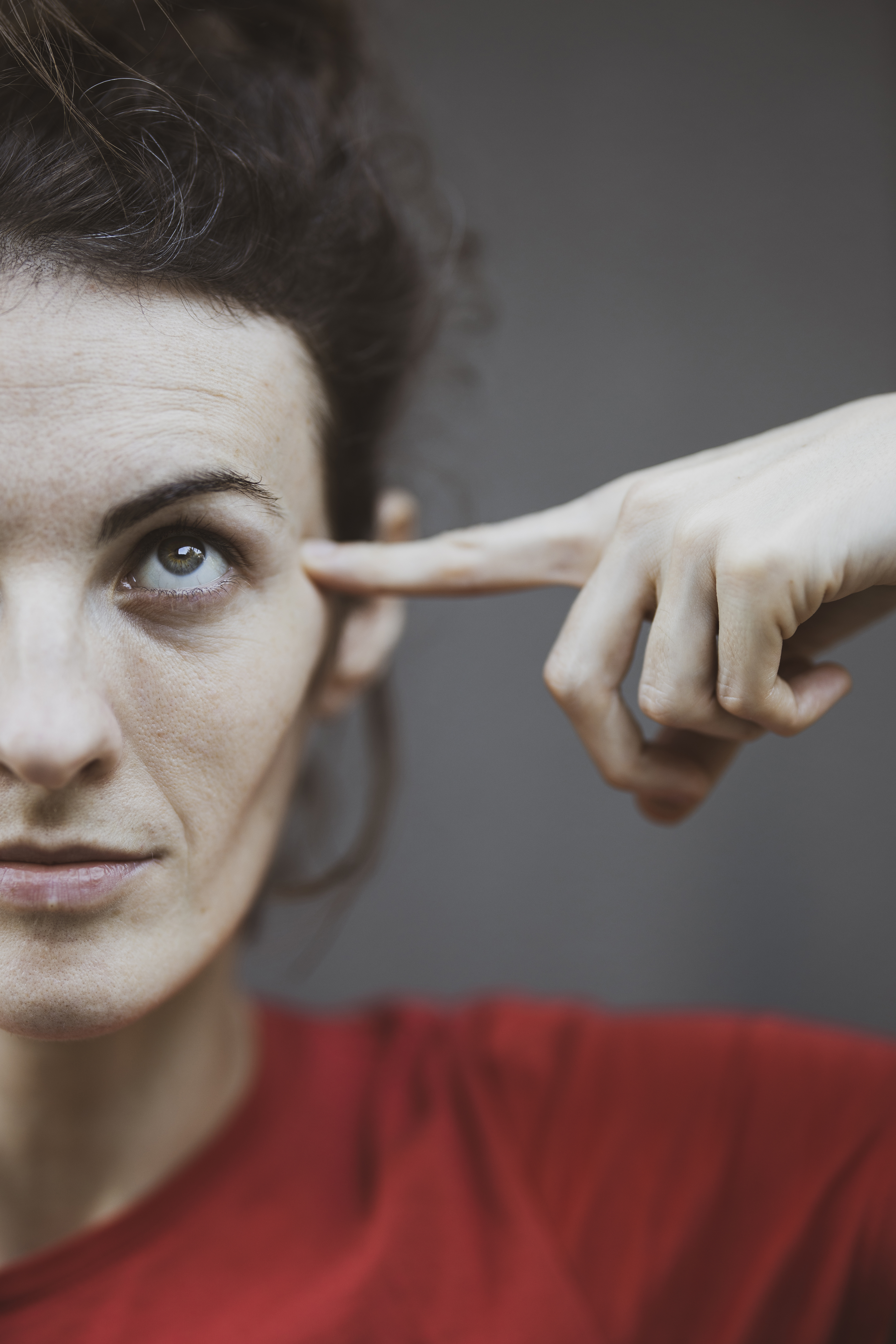 Selective Focus Portrait Photo of Woman in Red T-shirt Pointing to Her Head