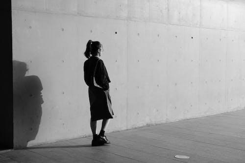Grayscale Photo of Woman Walking Near Wall