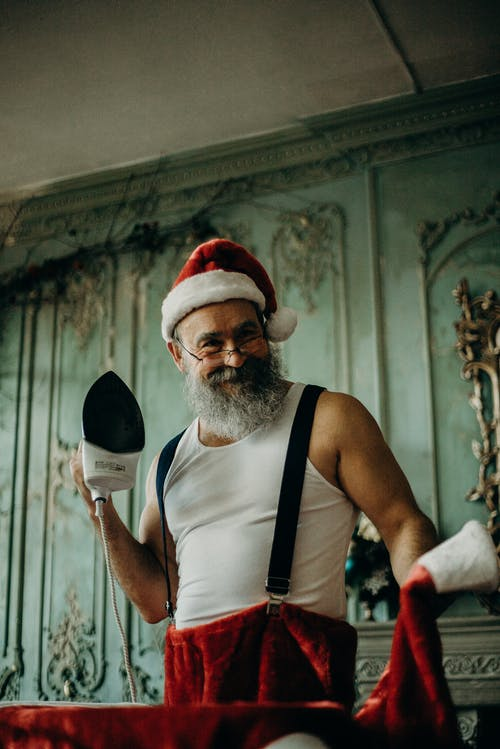 Man in Santa Claus Costume Holding Clothes Iron