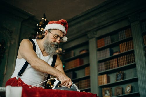 Man Wearing Santa Claus Costume Ironing Cloth
