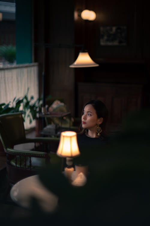 Woman in Black Shirt Sitting Beside Pendant Lamp