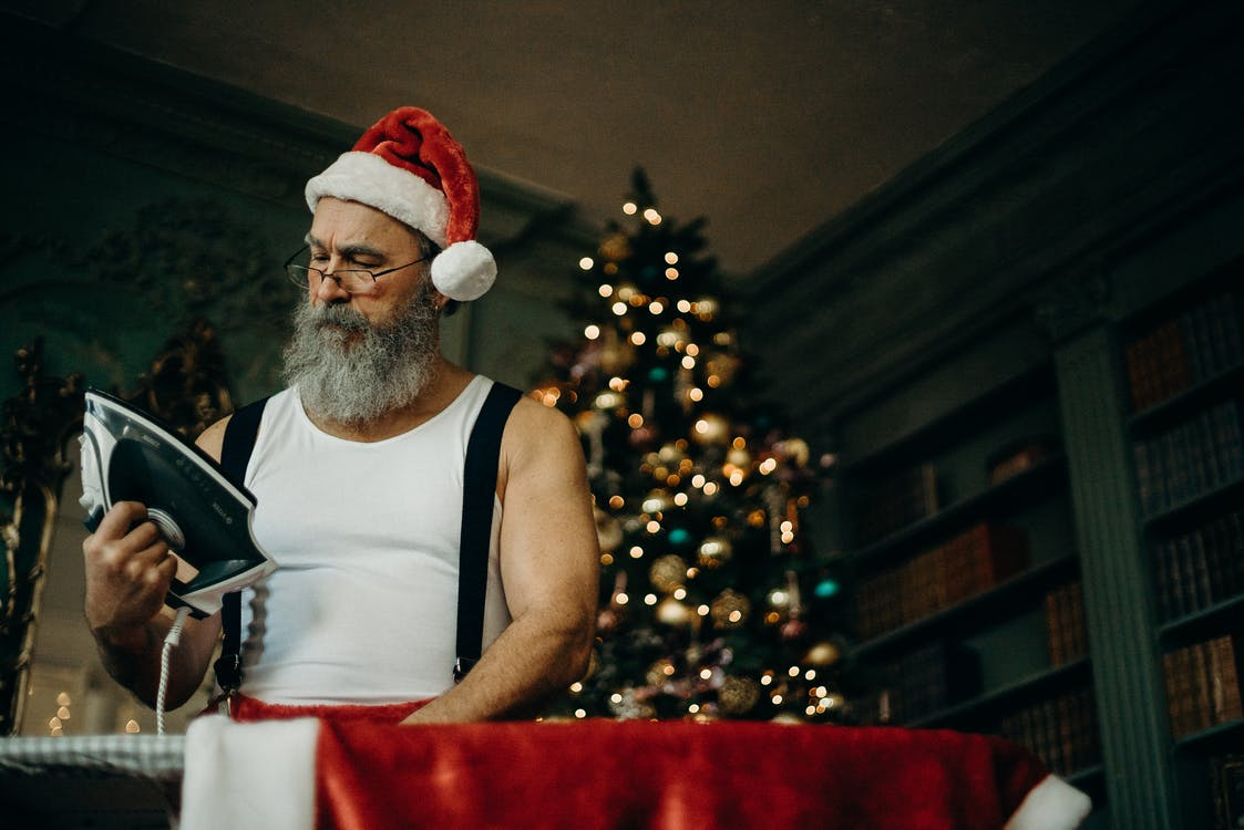 Man in White Tank Wearing Santa Hat Holding Black and Gray Dry Iron