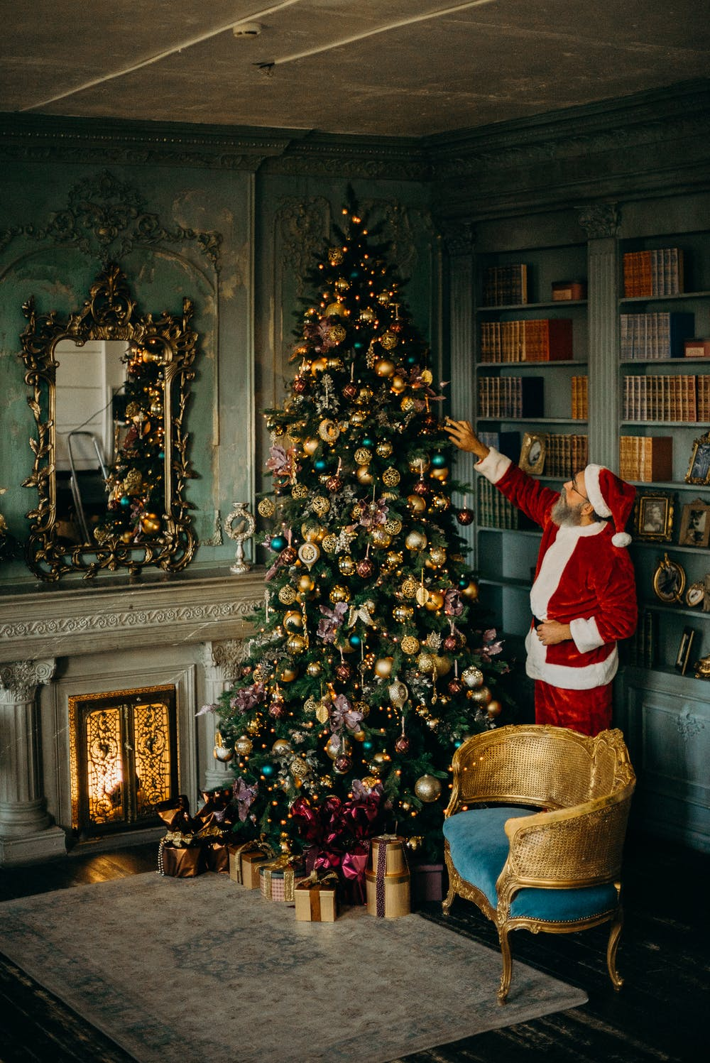 Santa Claus standing beside a Christmas tree. | Photo: Pexels