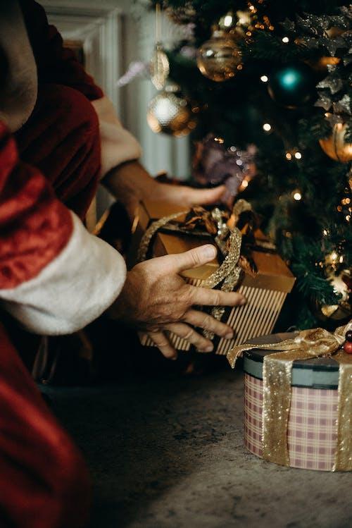 человек в костюме санта клауса с золотой подарочной коробкой