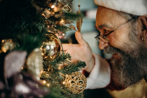 Man Looking at Gold Bauble