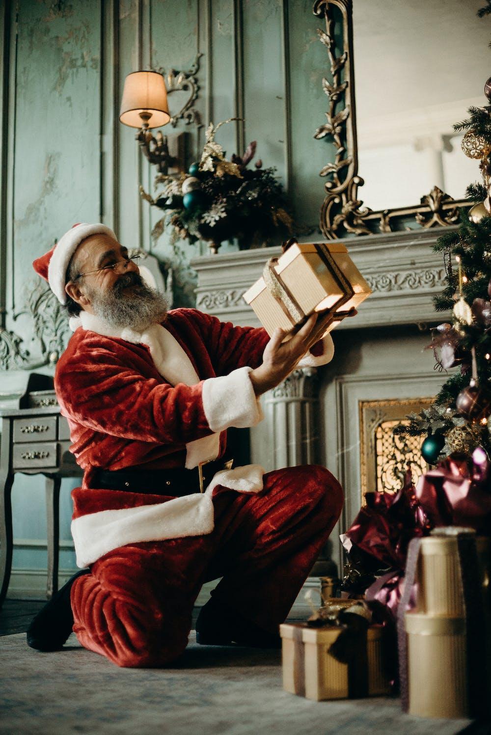 Santa Claus holding a gift box. | Photo: Pexels