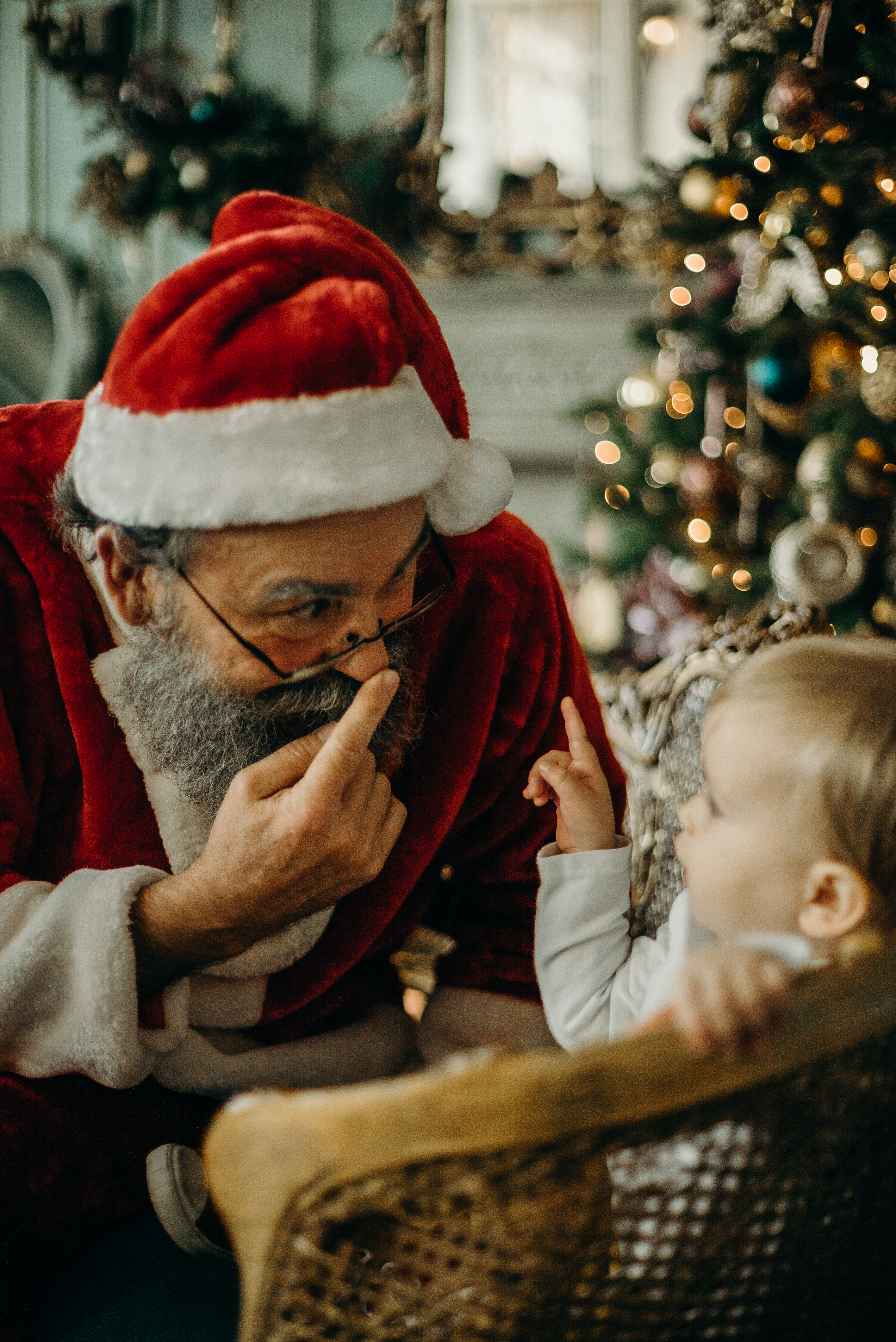 Man in Red Santa Claus Costume Standing Beside Toddler
