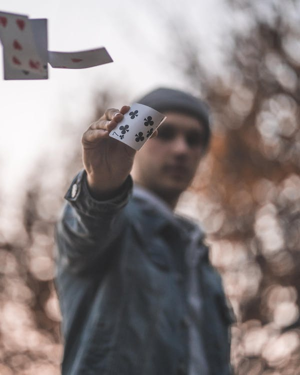 Burred Photo of a Man Holding Ace Playing Card