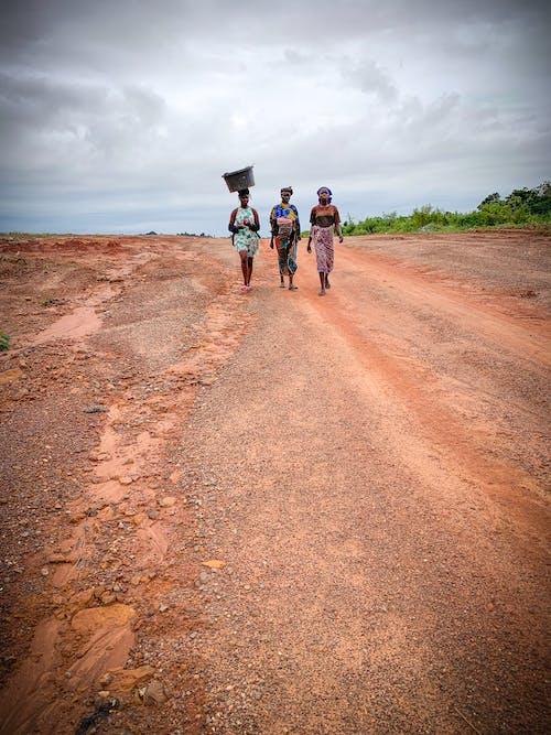 Women Wearing Multicolored Dress Walking on Sands Pathway