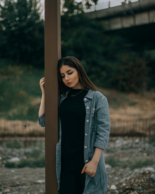 Woman Standing Beside Brown Wooden Post