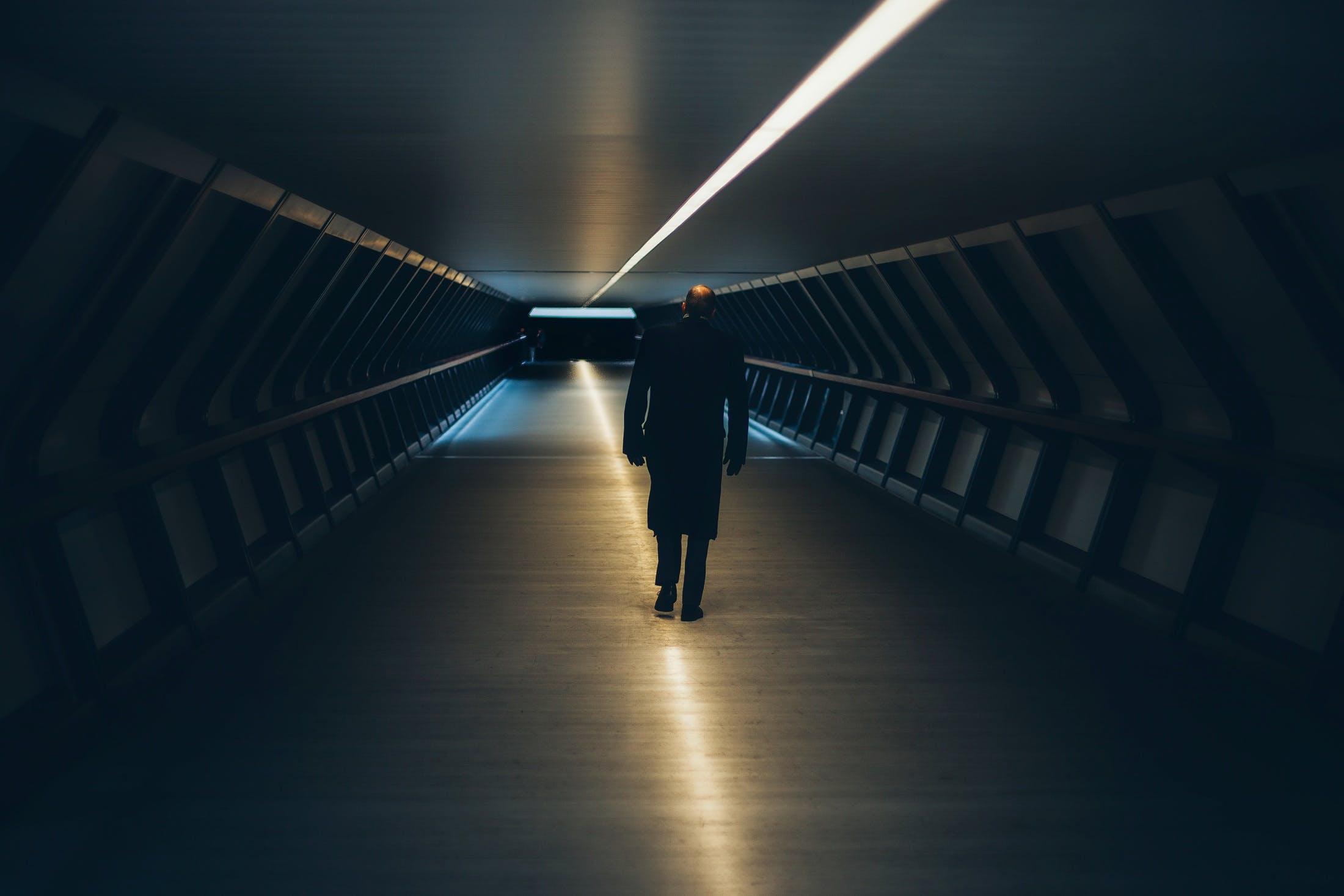 Man on Escalator in Illuminated Room