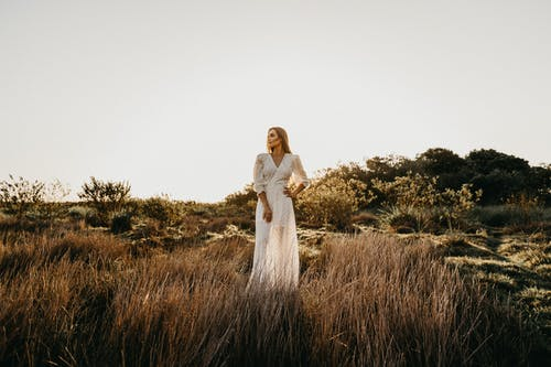 Woman in White Dress Standing on Grassy Field