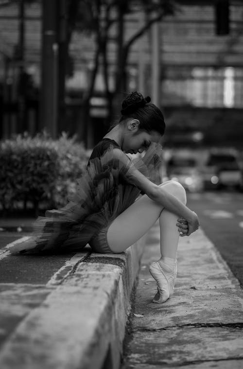 Black and White Photo of Ballerina Sitting on the Street