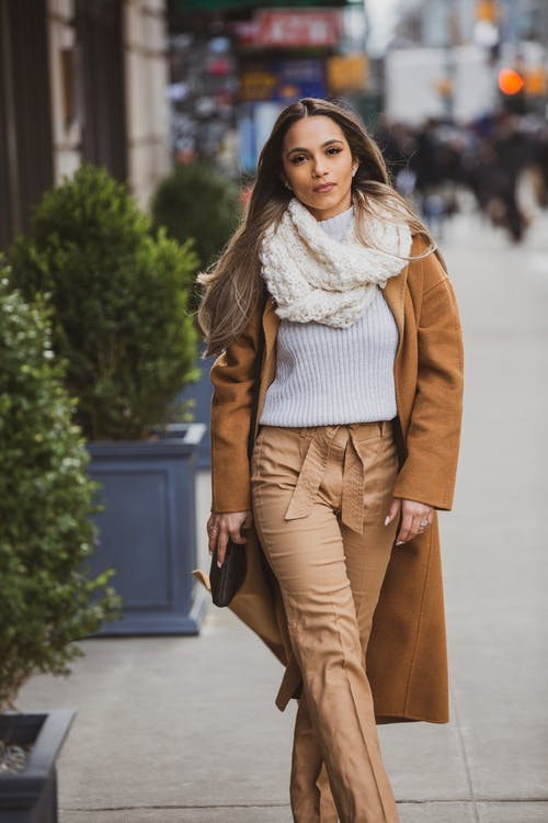 Selective Focus of a Woman in Brown Coat and Trousers Walking on the Sidewalk