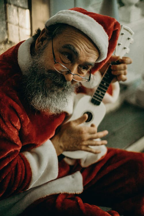 Man Wearing Santa Claus Costume Holding White Ukulele