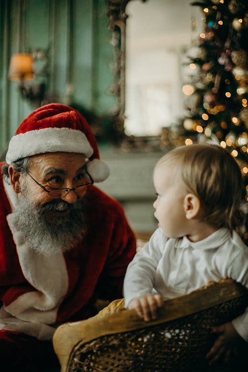 Man In Santa Claus Costume Looking at a Baby
