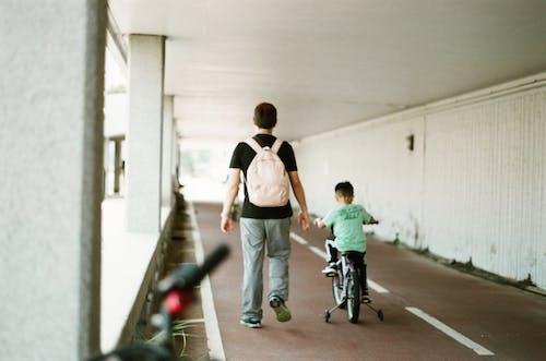 Man Walking Beside Boy Riding Bicycle