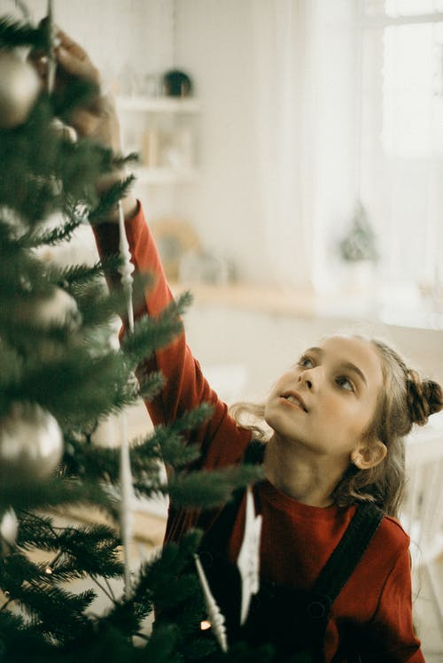 Girl Reaching The Top Of A Christmas Tree