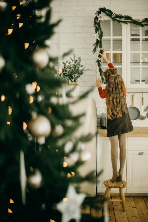 Girl Putting A Christmas Decoration