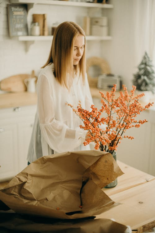 Woman Arranging Flowers On A Vase