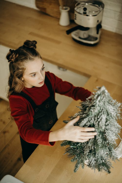 Girl Putting A Christmas Tree Decoration On Counter Top