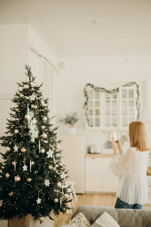 Woman Taking Photo Of Christmas Tree