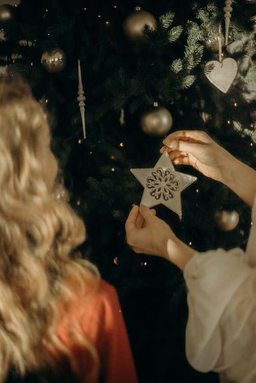 Girls Putting Ornaments On A Christmas Tree