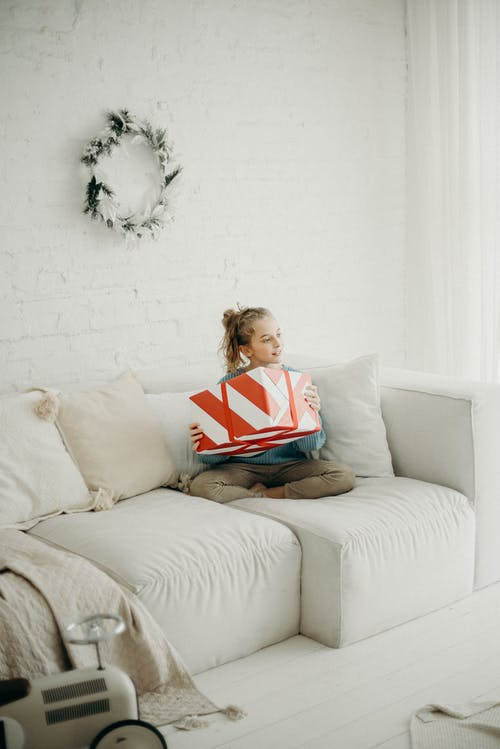 Photo of Girl Sitting on White Sofa with Her Legs Crossed Holding Present