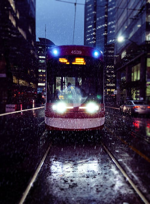 Red and White Tram On A Rainy Night