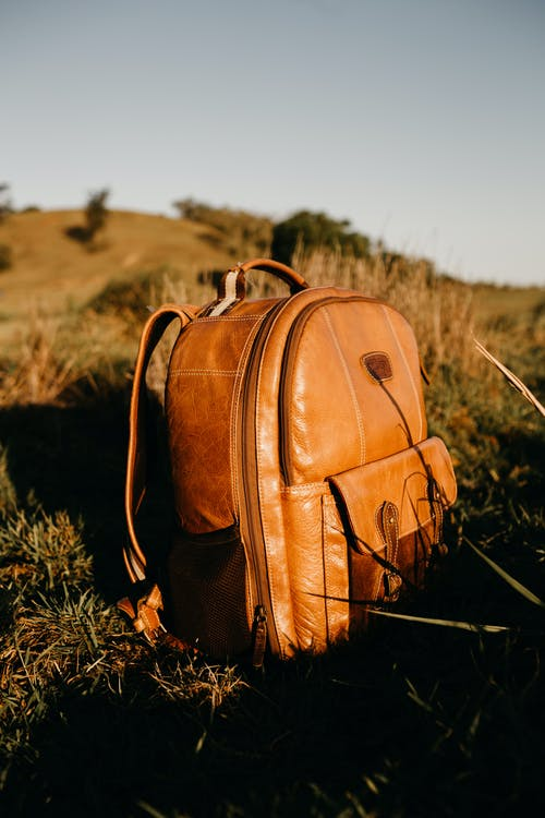 Brown Leather Backpack On A Grassfield