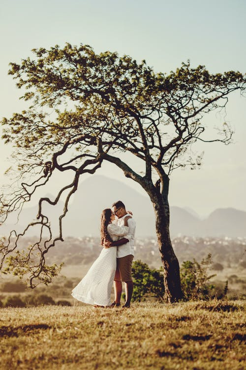 Man and Woman in Holding Each other Standing Beside Tree
