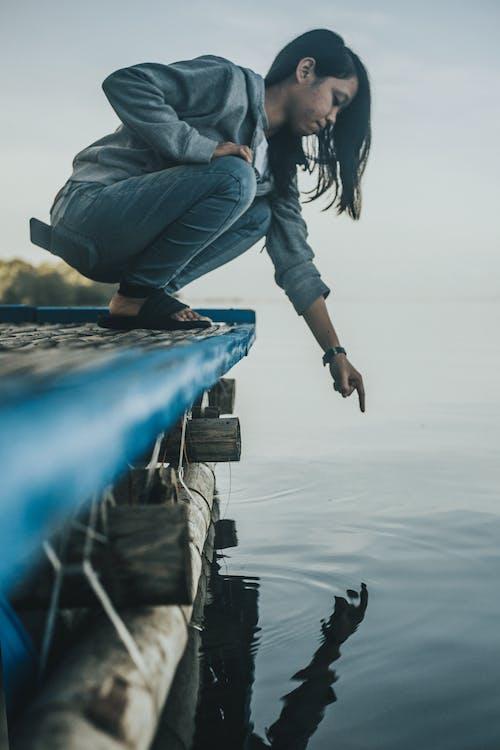 çömelme, deniz, göl, Kadın içeren Ücretsiz stok fotoğraf
