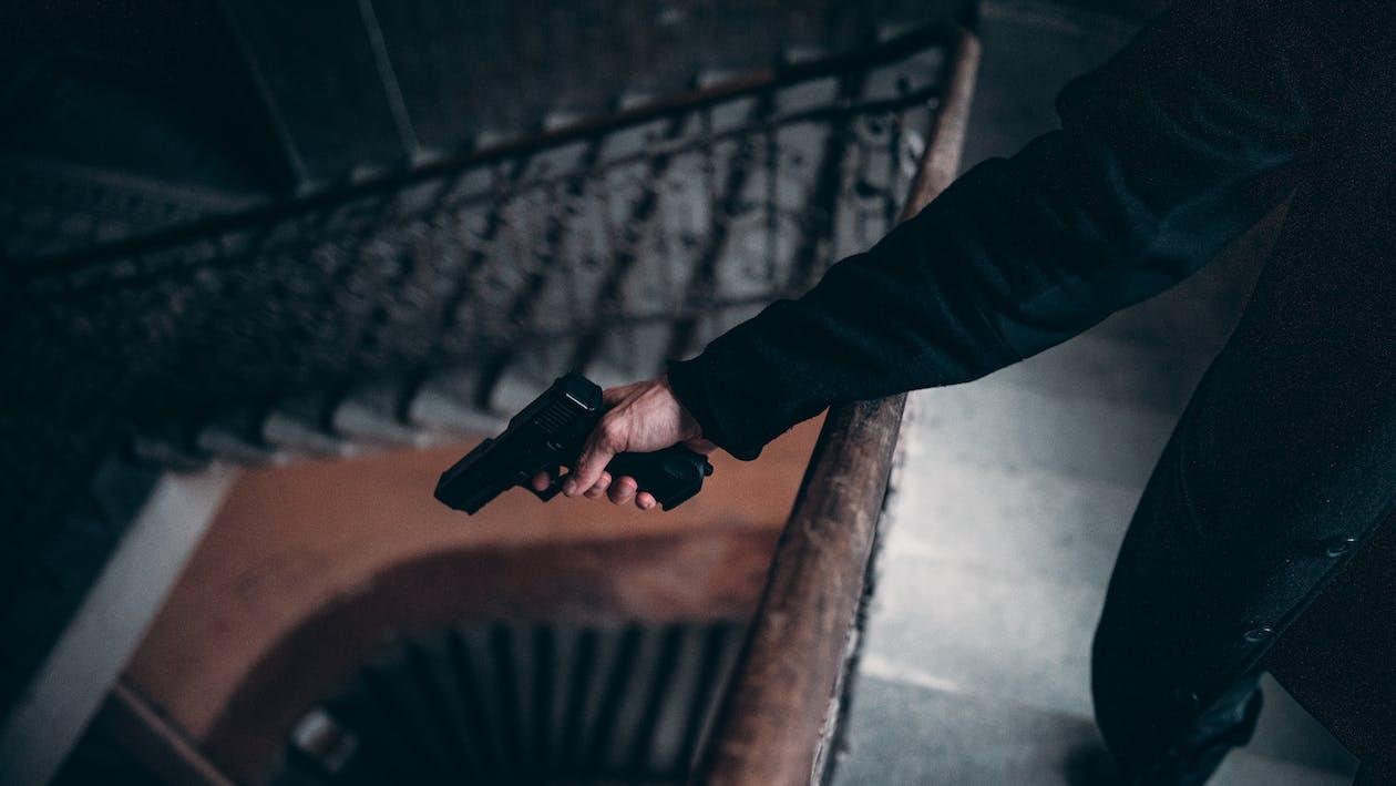 Person Holding Black Semi-automatic Pistol