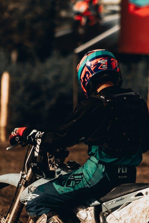 Unrecognizable motorcyclist riding motorbike on street