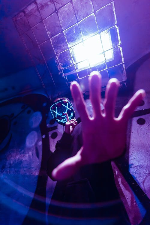 Low Angle Photo of Person Wearing LED Mask While Doing Silence Gesture
