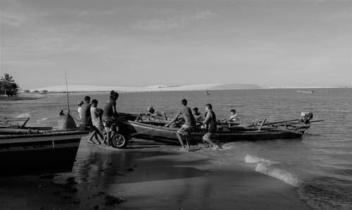 Grayscale Photography of People Pulling Boat on Shore