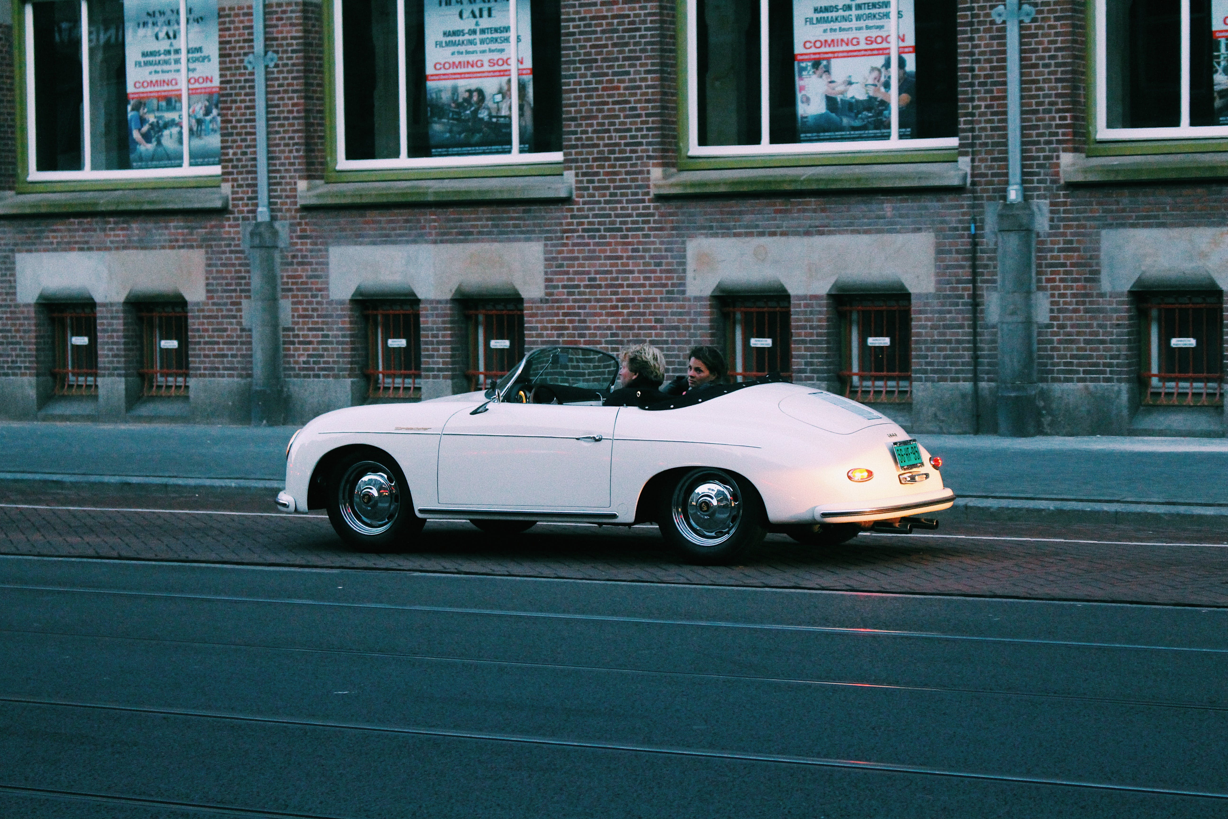 Two People Riding White Classic Convertible Car