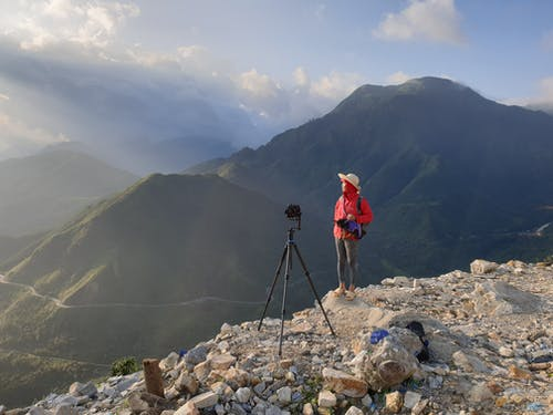Person Wearing Red Jacket Standing on Cliff Beside Black Camera Tripod