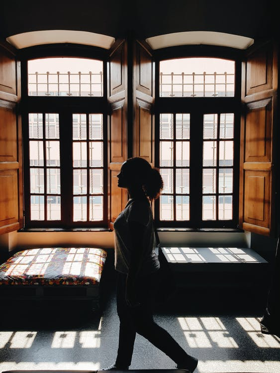 Silhouette of Woman Walking Past Windows