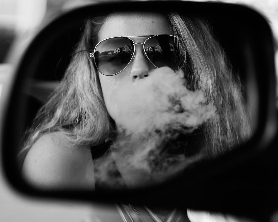 Reflection of Woman Releasing Smoke from Mouth