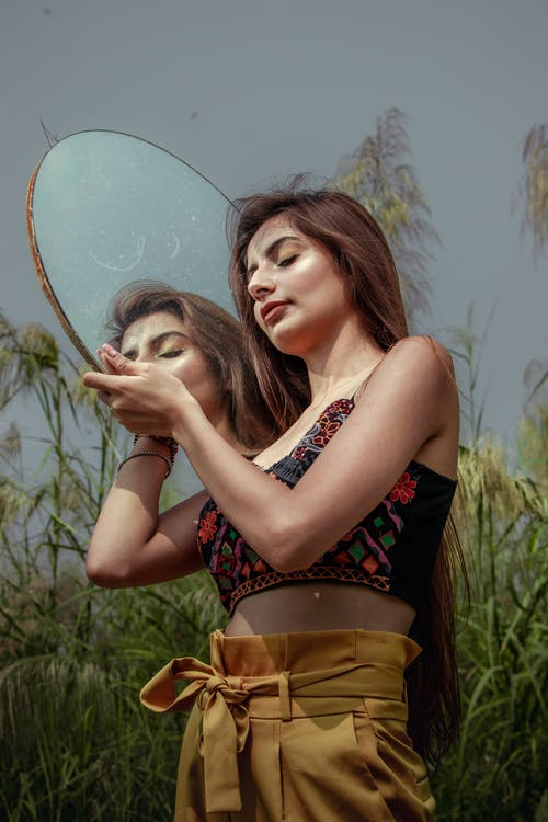 Woman Wearing Crop Top While Holding a Mirror
