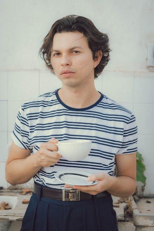 Man Holding White Ceramic Cup