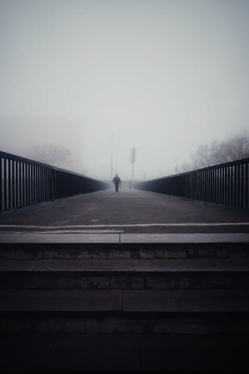 Person Walking on Footbridge