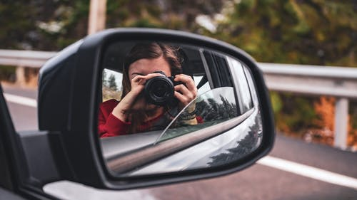 Woman Taking Photo of Car's Side Mirror