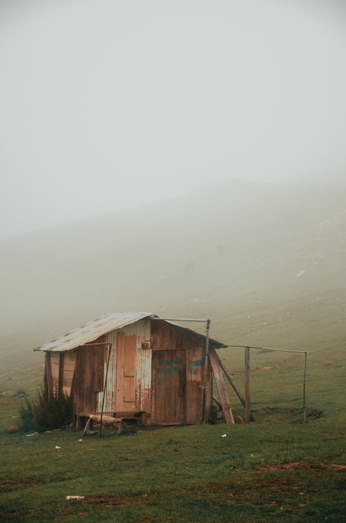 Wooden House on Grass Field During Foggy Weather