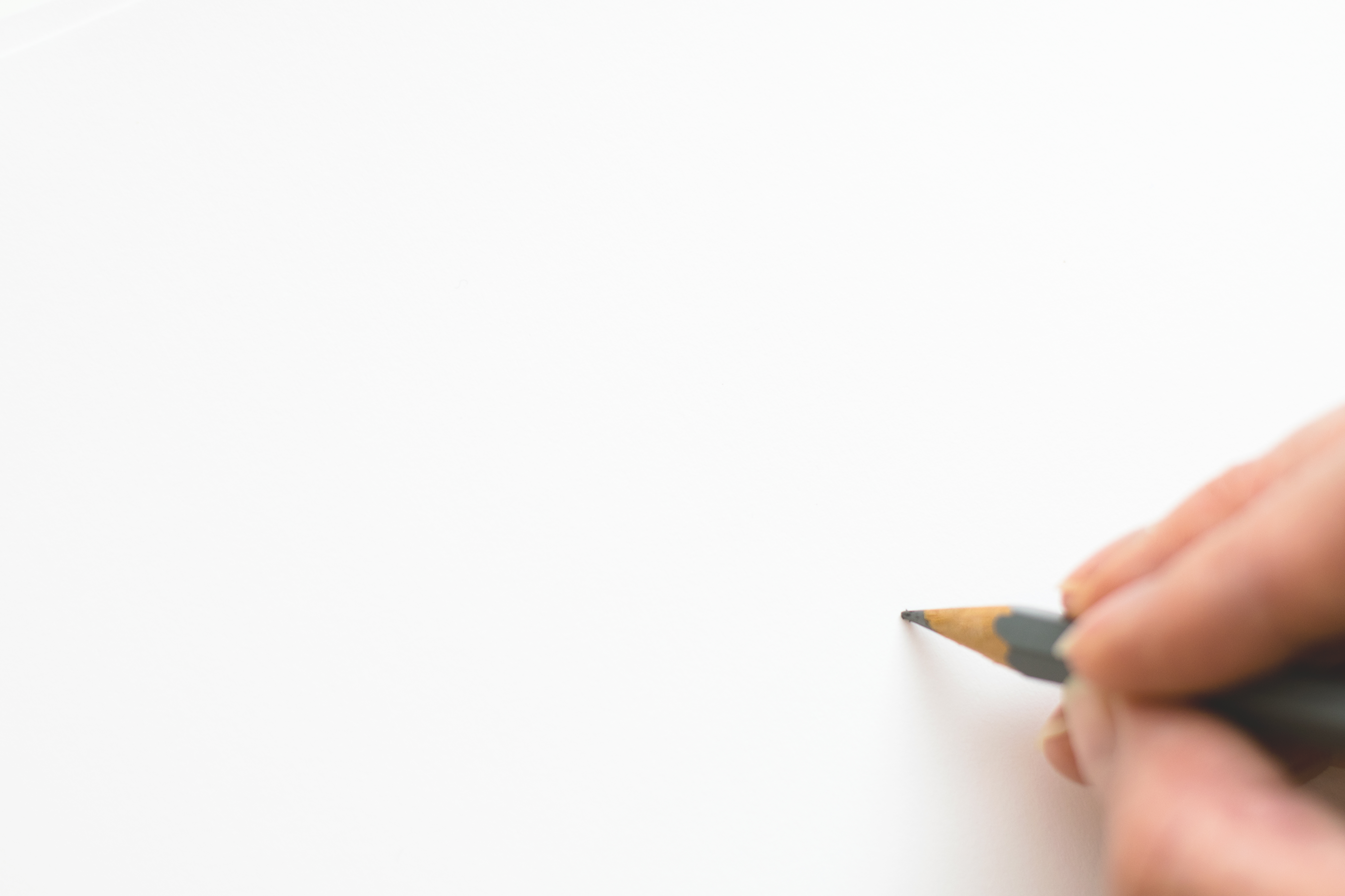 Close-up of Hand Holding Pencil over White Background