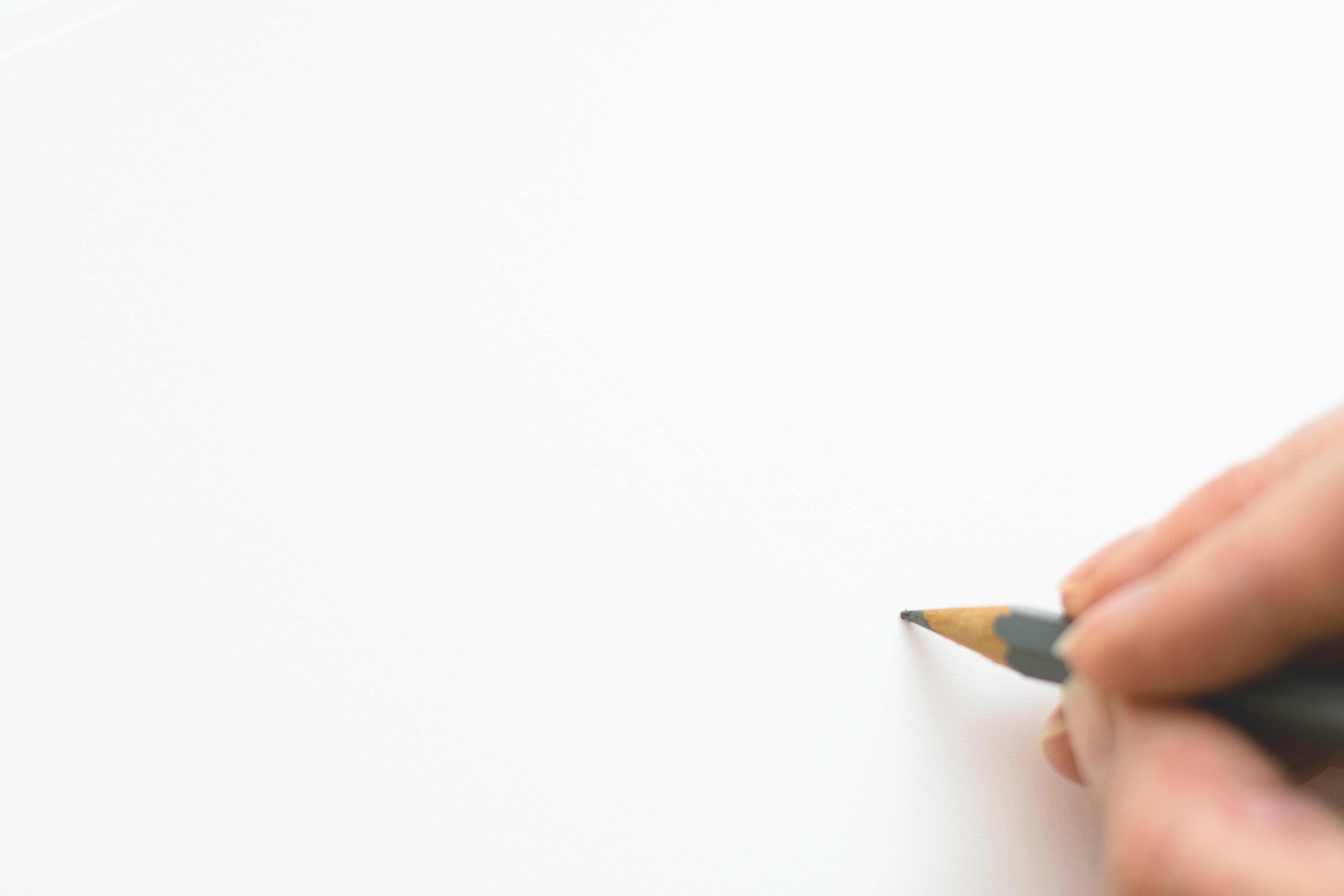 white background. close-up of hand holding pencil over white background s