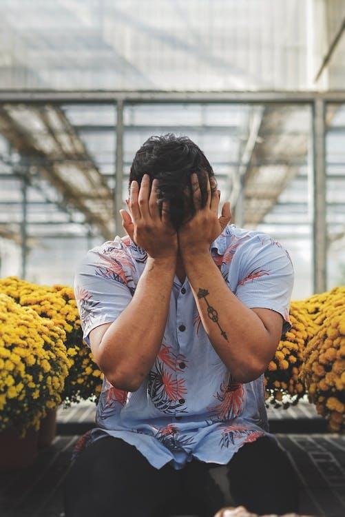 Uomo In Camicia Floreale Che Copre Il Viso Con Le Mani Sedute Tra Fiori Gialli In Vaso