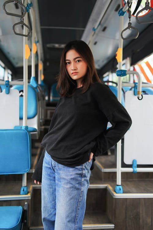 Woman in Black Sweater and Blue Jeans Standing Inside Vehicle