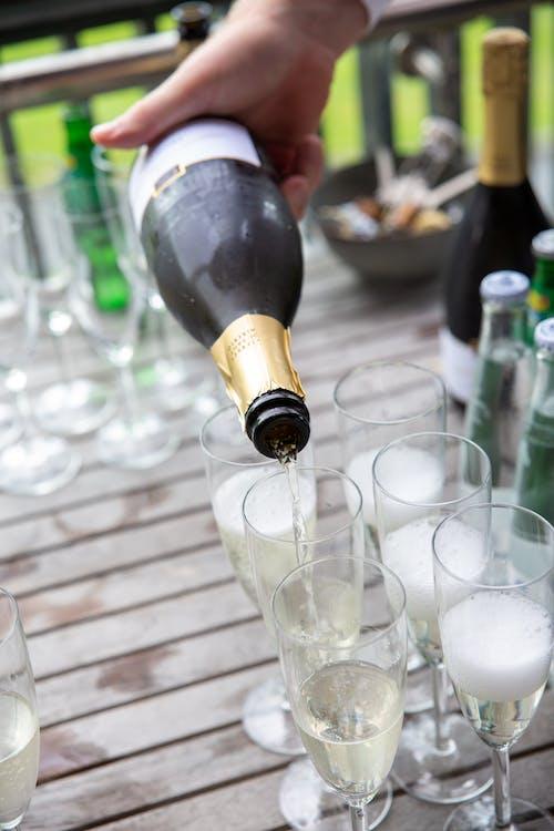 Person Pouring Champagne into Glasses